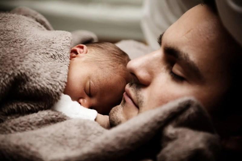 tata spi z dzieckiem na piersi