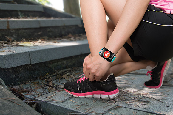 Sport woman hand tying shoelaces wearing touchscreen smartwatch with health sensor app icon on forest trail background