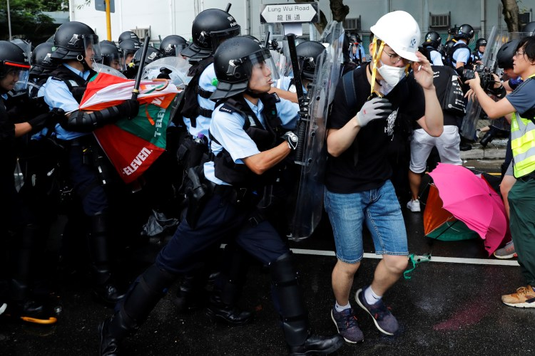 Police try to disperse protesters near a flag raising ceremony for the anniversary of Hong Kong handover to China in Hong Kong