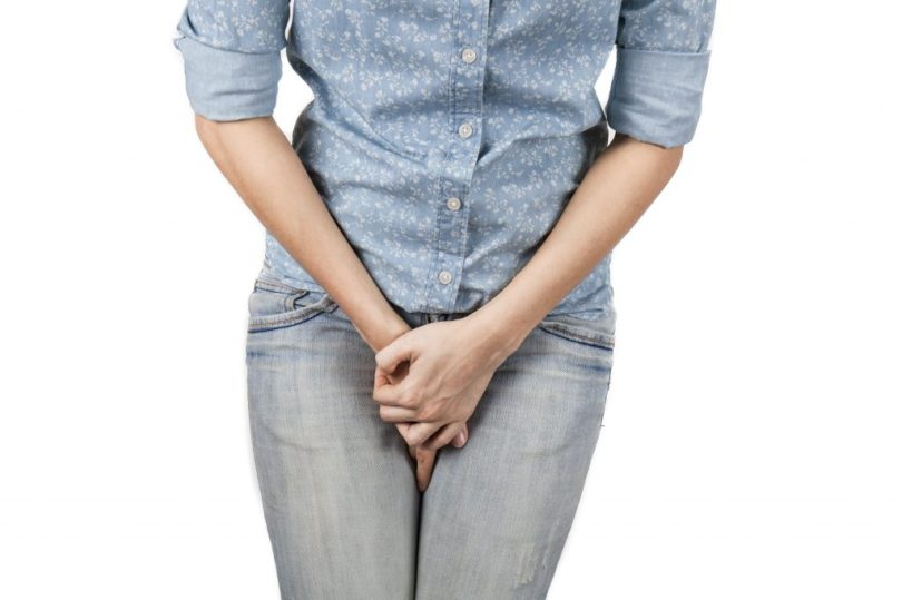 Close up of a woman with hands holding her crotch isolated in a