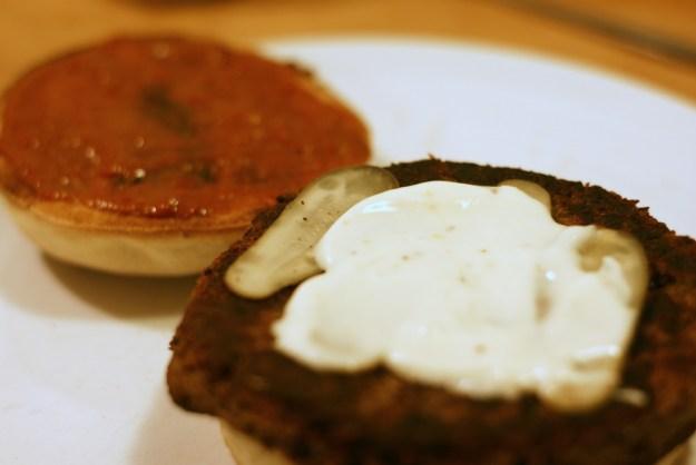 Na sodnieje części kładziemy burgera, na niego korniszony i majonez. Wierzchnią część bułki smarujemy ketchupem z dodatkiem ostrego sosu.