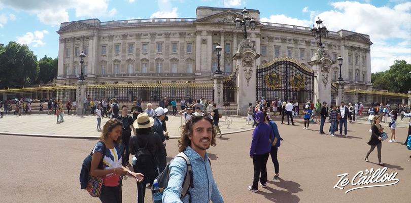 Contempler le palais royal à Londres, le Buckingham palace, et ses grandes grilles dorées.