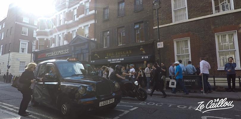 Prendre un taxi face à un pub anglais dans le quartier de Londres.