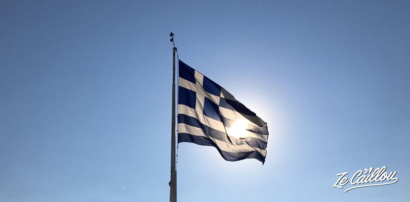 Drapeau grec qui vole au soleil à l'acropole à Athènes.