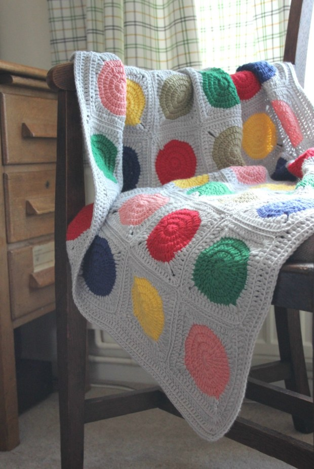 Bright crochet baby blanket. Crochet circles in squares.