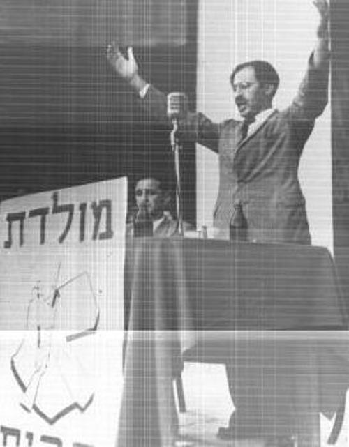 בגין באספת בחירות. ברקע ציור ארץ ישראל משתי גדות לירדן