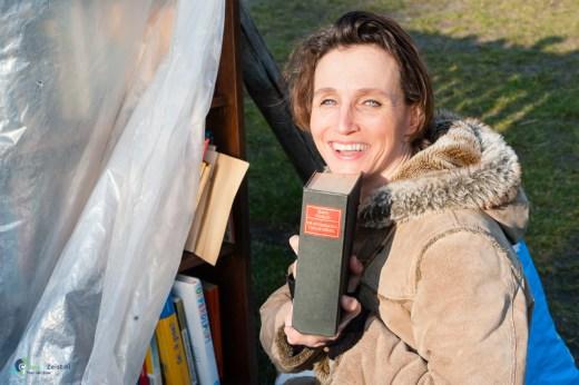 Liesbeth van Schaik zet boeken in de gemeenschappelijke boekenkast in de Allegrotuin