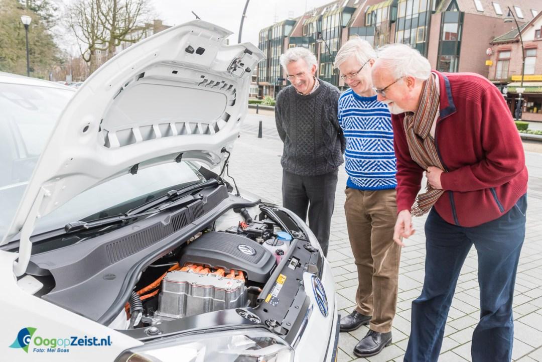 Wethouder Varkenvisser bekijkt de electrische motor van de dienstauto.