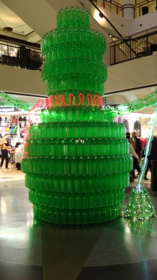 A giant green snowman made out of recycled soda bottles.