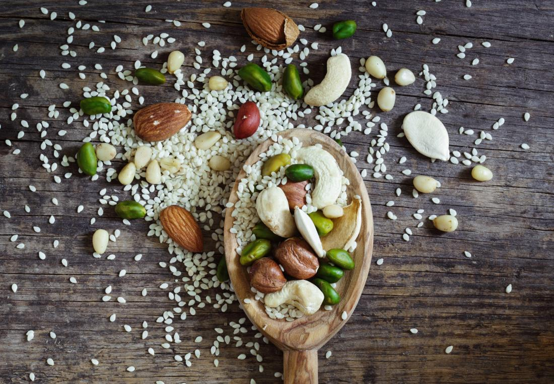 mixed nuts and seeds on wooden spoon over table including pine nuts almonds pistachios and cashews