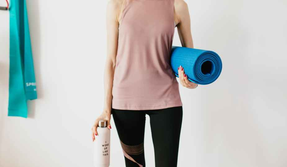 crop sportswoman carrying sport mat and bottle of water before exercising