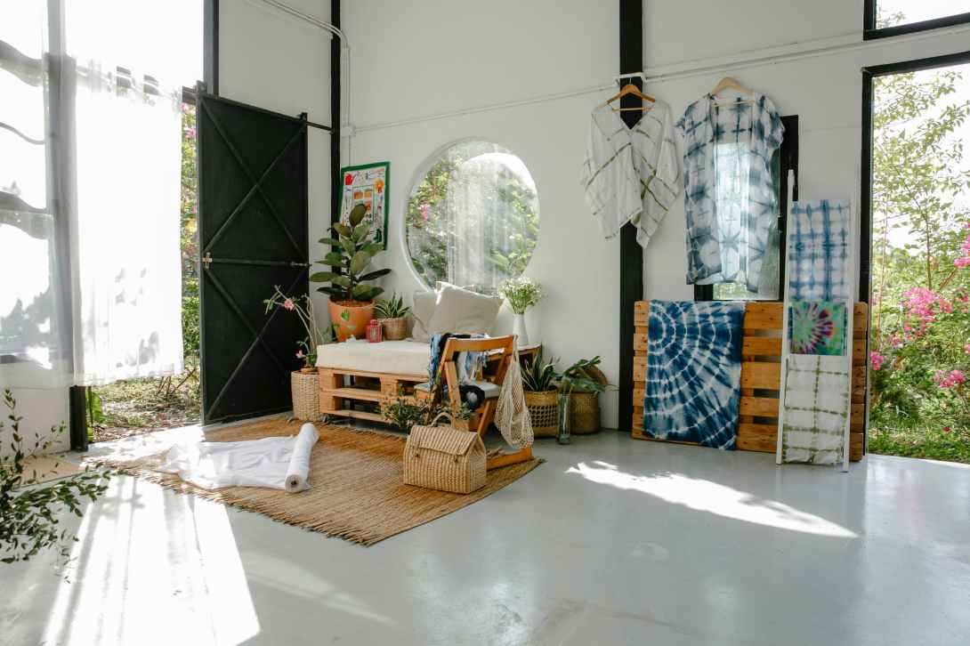 spacious atelier with wooden and wicker furniture and potted plants