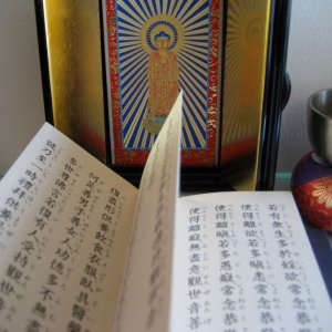 Japanese Buddhist altar with image of Amitabha Buddha and a copy of the Lotus Sutra.
