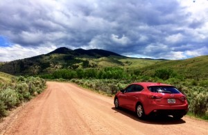 Photo of Red Mazda 3 iGrand Touring on dirt road with hills and cloudy sky ahead