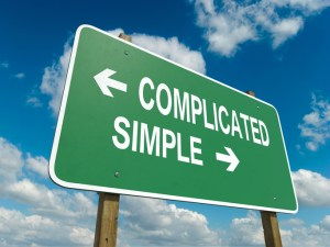 Simplify your life! A road sign with complicated simple words on sky background