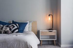Photo of made bed and side table (Photo by Christopher Jolly on Unsplash)