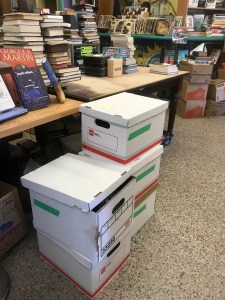 Five bankers boxes of books waiting for review and purchase at Chamblin's Bookmine