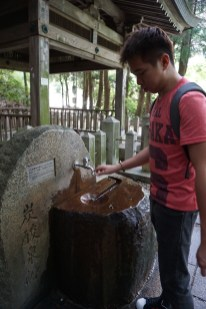My friend trying out the water at Tansan Sengen Koen