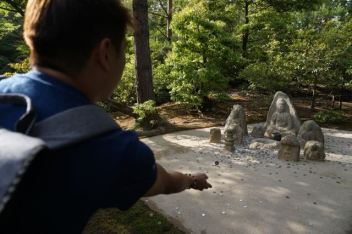 My friend tossing a coin for luck in Kinkakuji