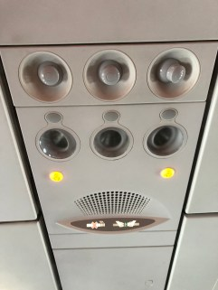 Air vent, reading lights are found on the ceiling above the seat