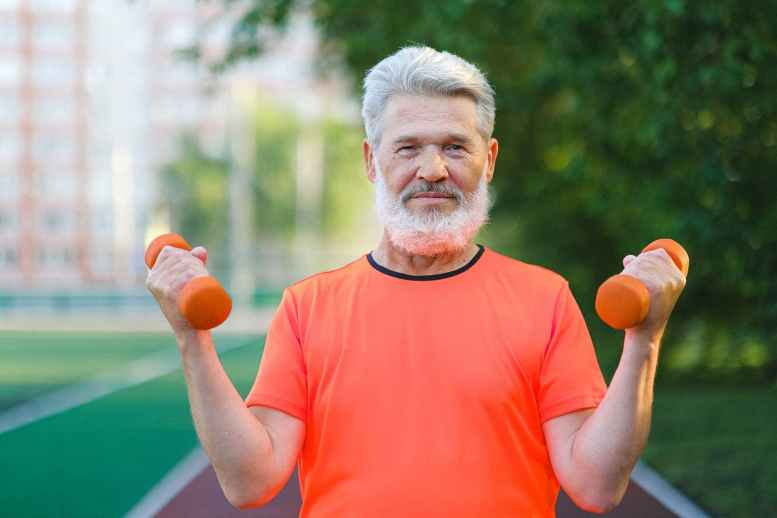 cheerful aged sportsman doing sport exercise