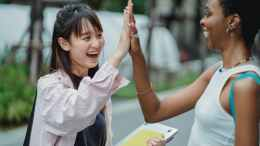 joyful diverse students giving high five in park