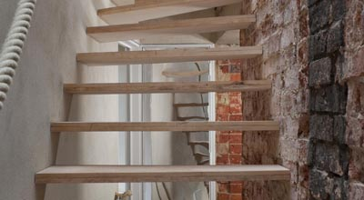 Wooden stairs with hemp handle and soot on wall at zero carbon house, Birmingham
