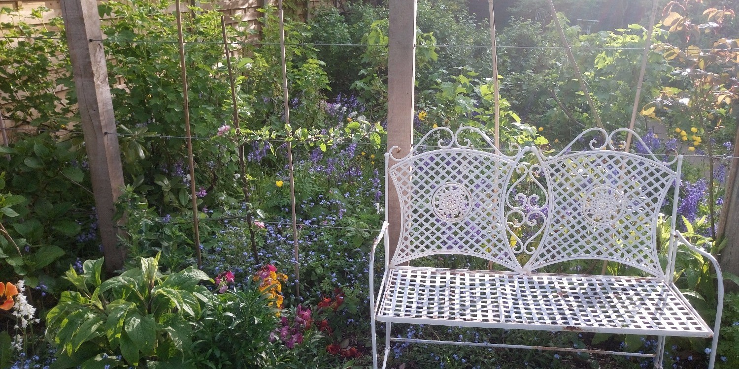 White seat in garden of zero carbon house Birmingham with sunshine and flowers