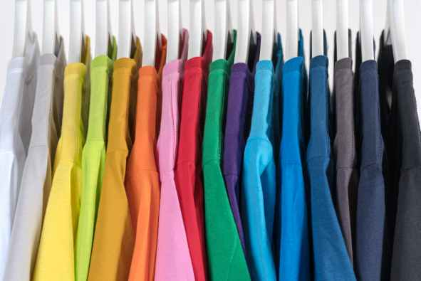 stylish collection of multicolored clothes on hangers in boutique