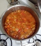 A large stainless steel pot of minestrone soup sitting on the oven