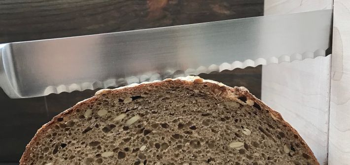 loaf of sourdough bread being sliced with a serrated knife