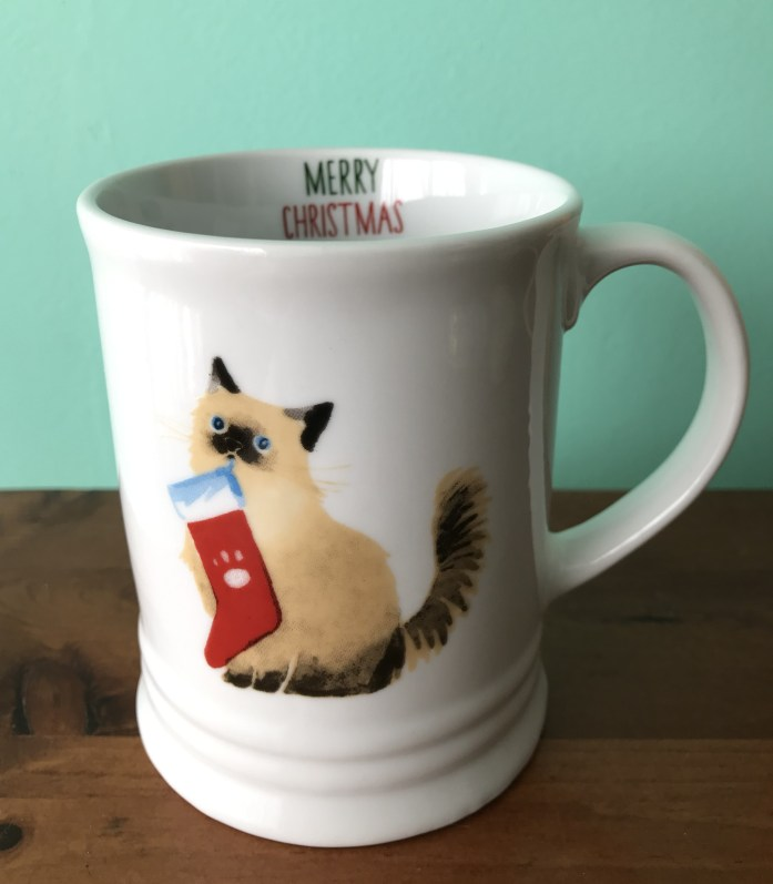 ceramic coffee mug with a cat holding a Christmas stocking in its teeth