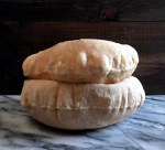 two freshly baked pitas filled with air, stacked one on the other