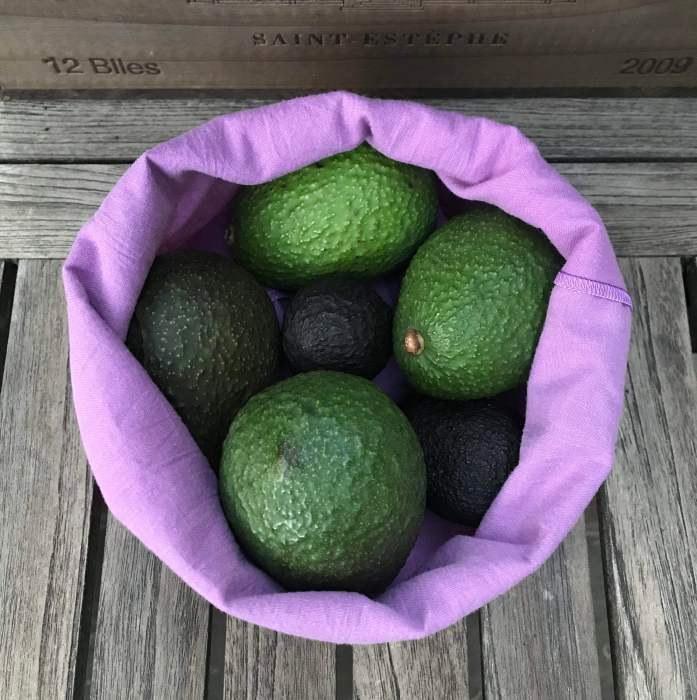 Purple produce bag upcycled from a donated linen sheet, filled with avocados