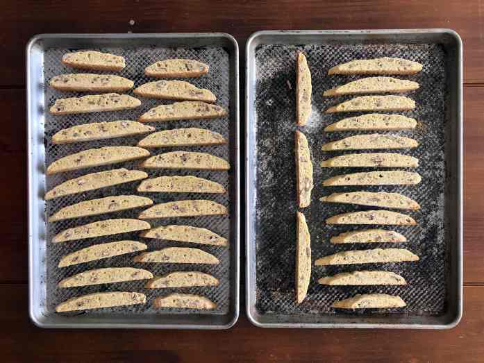 limoncello biscotti arranged on two baking sheets