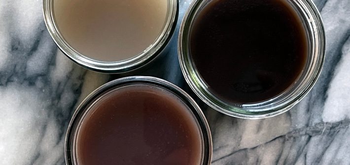 Three glass jars on a marble background, containing bean broth. They are pinto bean broth, black bean broth and kidney bean broth.
