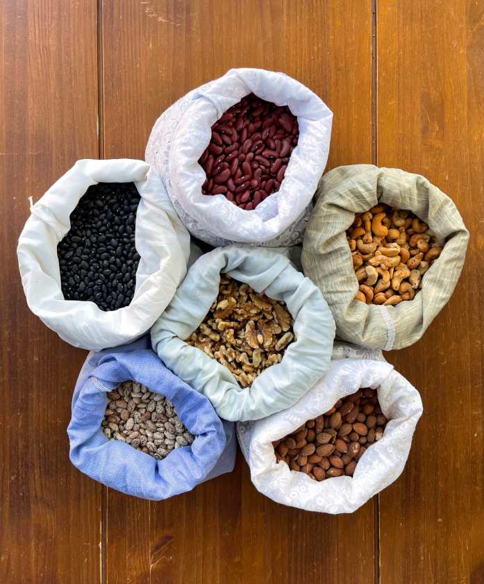 6 open cloth produce bags arranged on a wooden tabletop. The bags contain black beans, kidney beans, cashews, walnuts, pinto beans and almonds. Beans are a delicious component in frugal dinners.