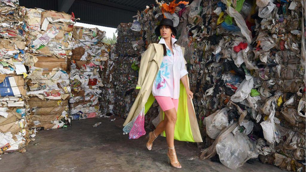 A woman walks through trash and landfill pollution