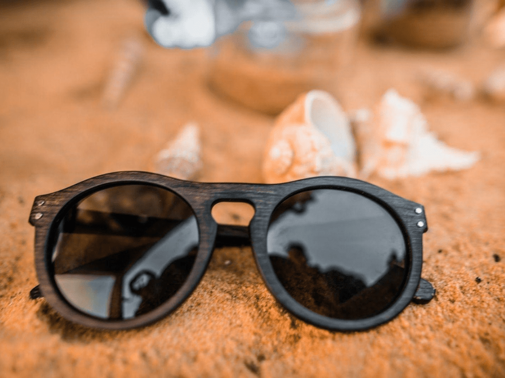 A pair of COCO LENI sustainable sunglasses on the sand