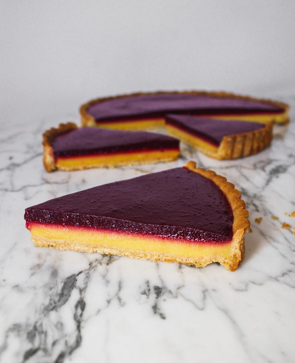 Tart slices, with yellow and purple layers, set on top of a marble surface.