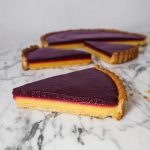 Tart slice with yellow and purple layers, set on a gray plate on top of a marble surface.