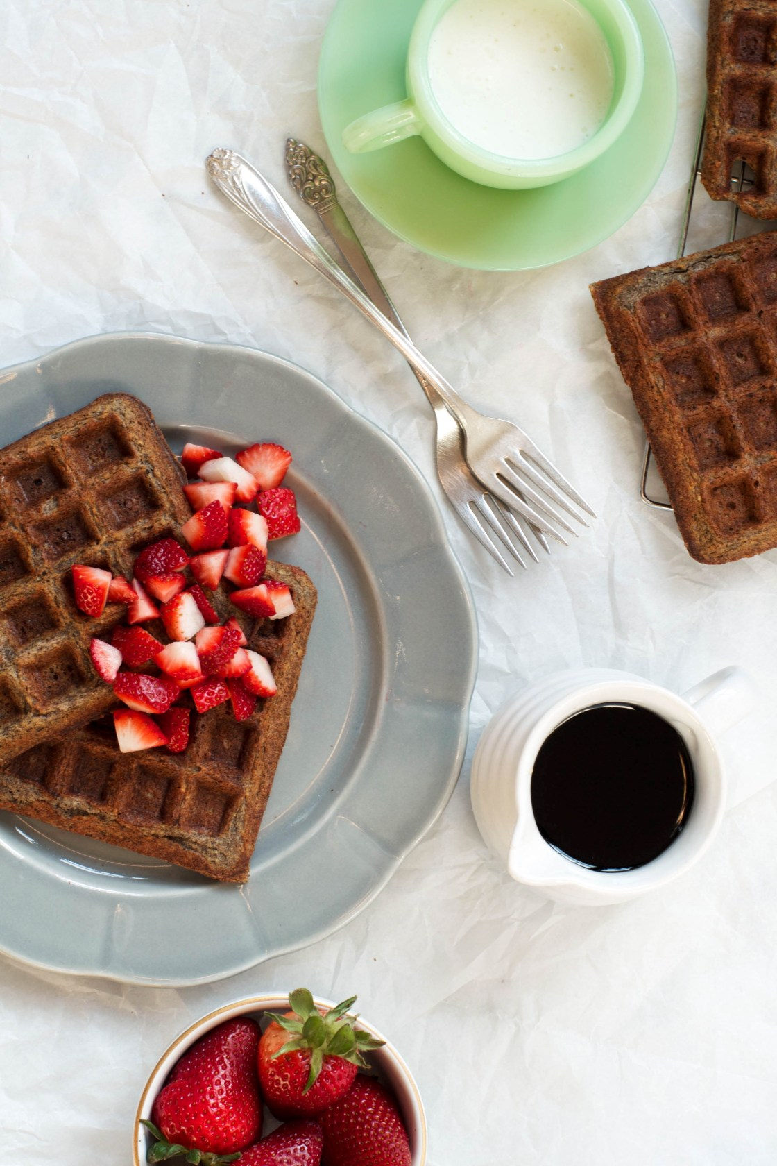 Gluten Free Buckwheat Waffles set on a gray plate with strawberries | Zestful Kitchen