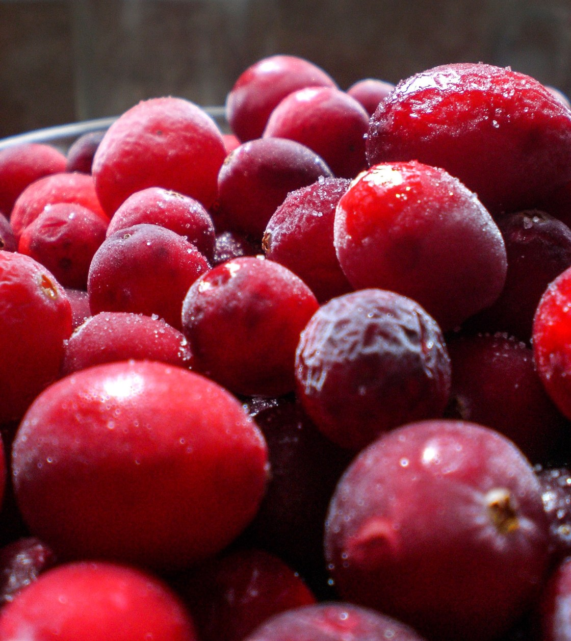 Frozen cranberries in a glass bowl.