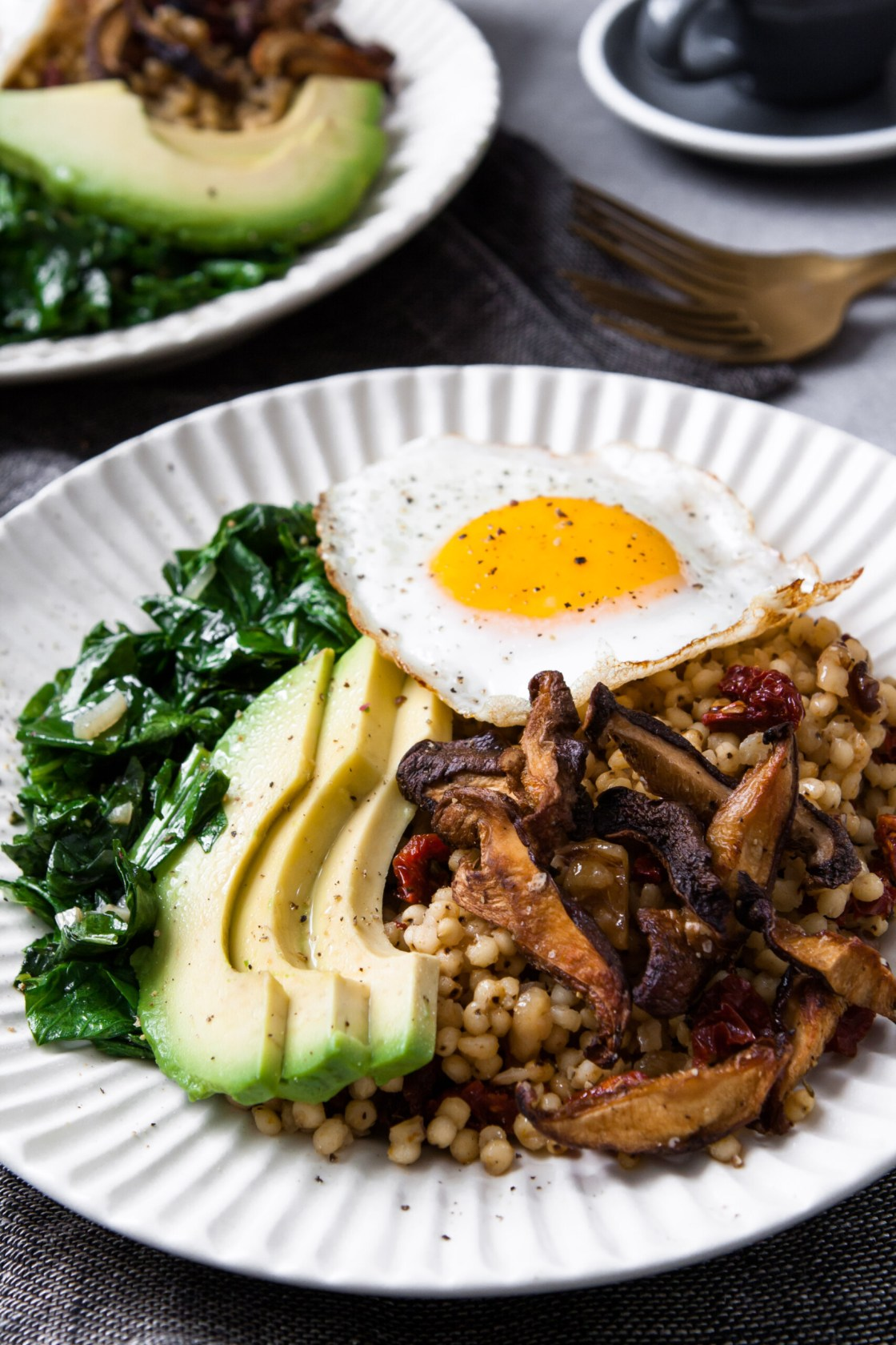 A simple winter breakfast bowl featuring garlicky greens, fragrant sun-dried tomato sorghum, and crispy shiitake mushrooms, topped with avocado and an over-easy egg, this is one healthy and flavorful breakfast. | from Lauren Grant of Zestful Kitchen