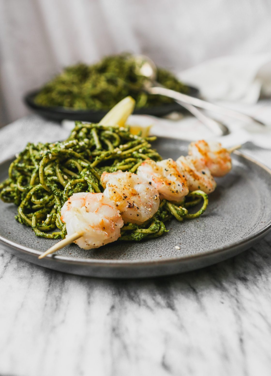 black plate with green pesto-covered pasta on top of marble with cooked shrimp on a skewer