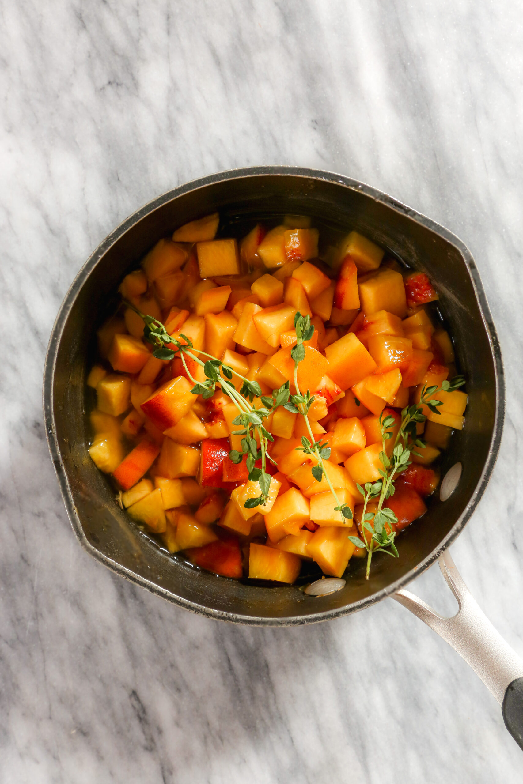 Diced peaches and fresh thyme sprigs in a saucepan set on a marble surface.
