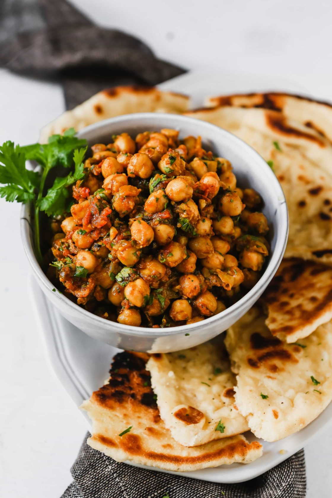 chickpeas and tomatoes in a white dish set on a white plate with homemade naan bread.