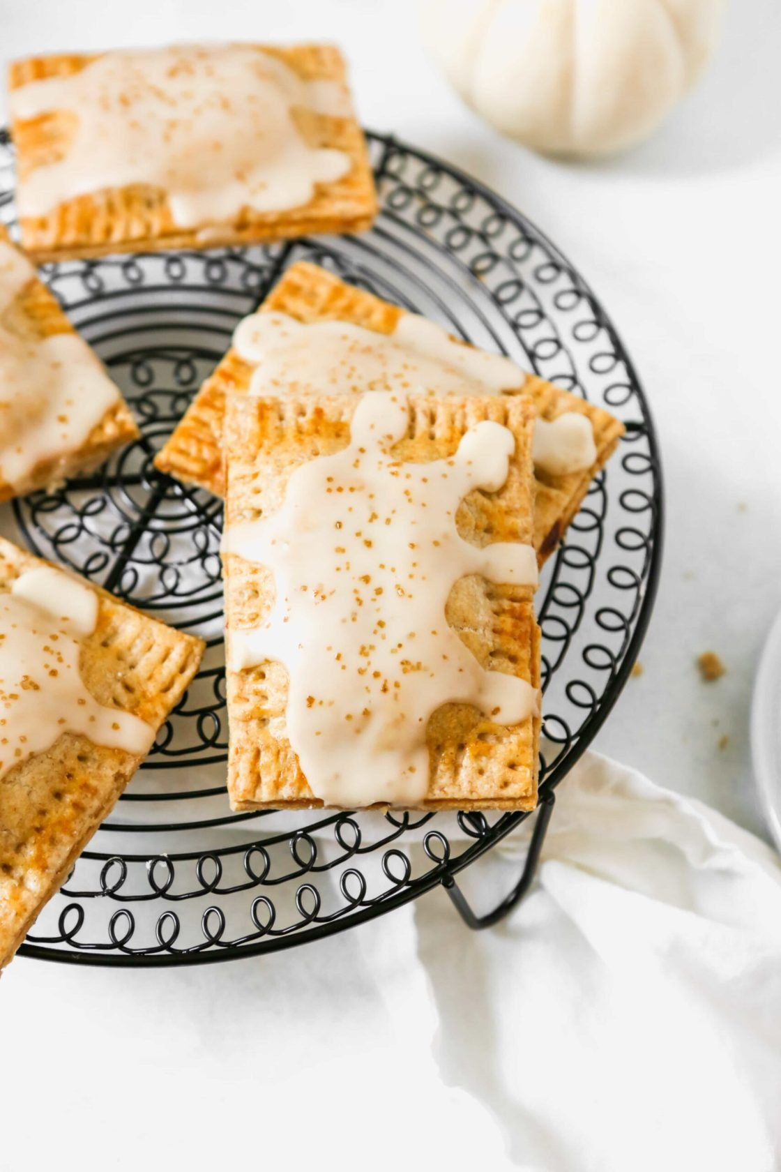 Homemade pumpkin butter pop tarts set on a black wire rack.