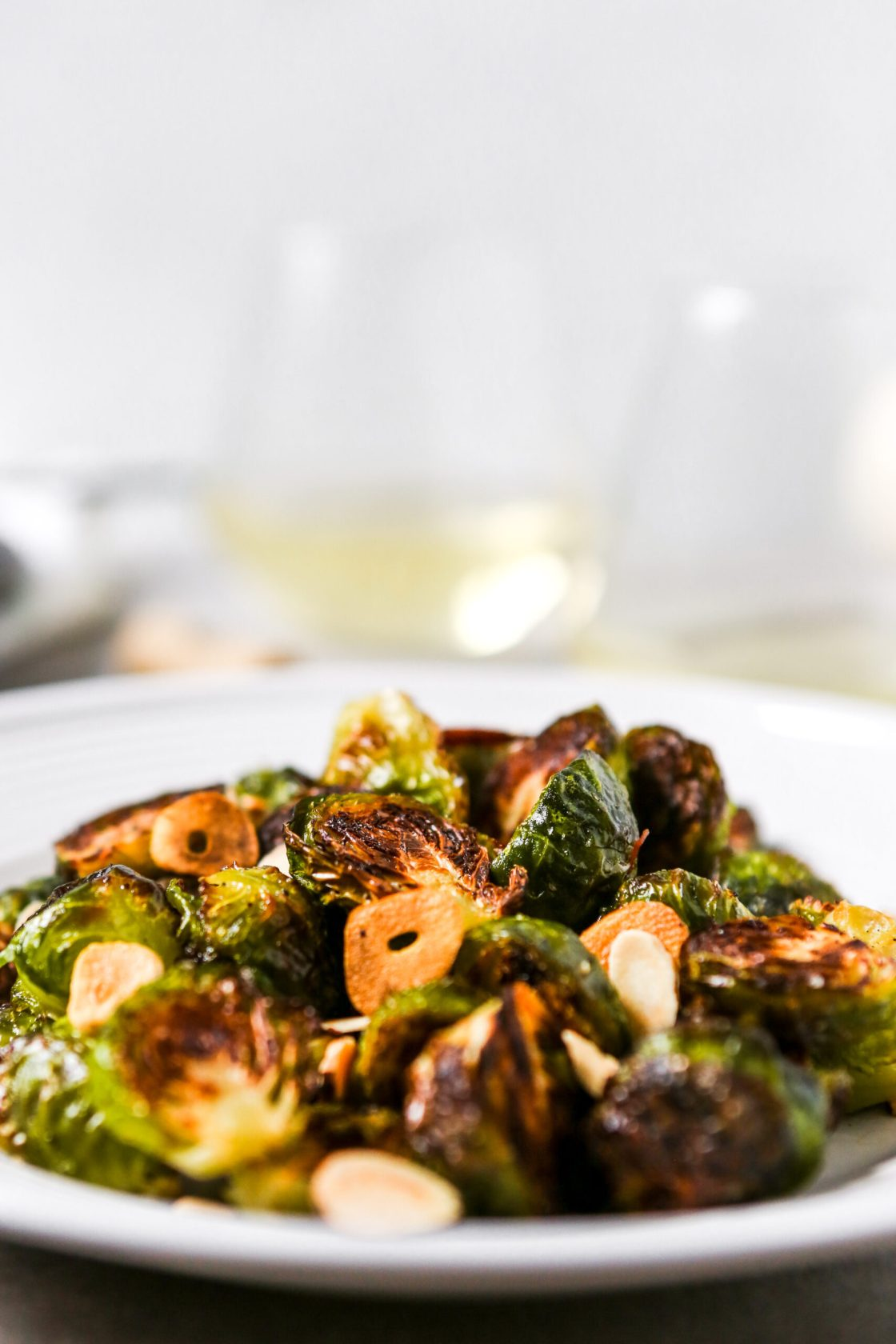 deeply roasted Brussels sprouts on a white plate.