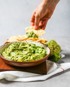 A large bowl of guacamole set on a cutting board with corn chips. Hand dipping chip in guacamole.